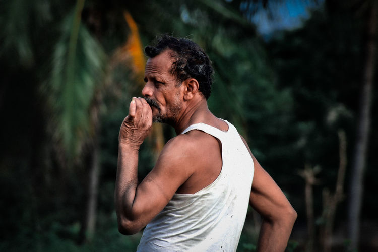 Side view of man smoking cigarette while standing against trees