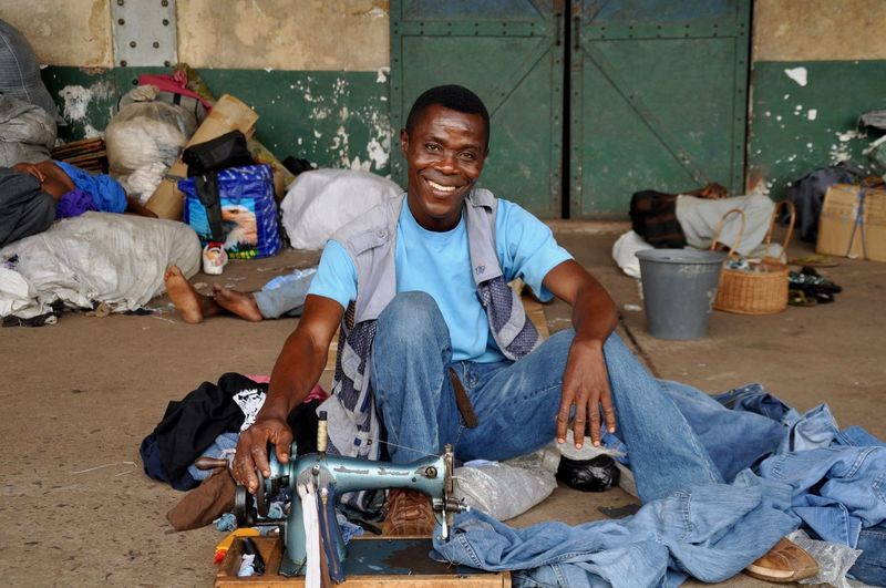 Portrait of man sewing jeans