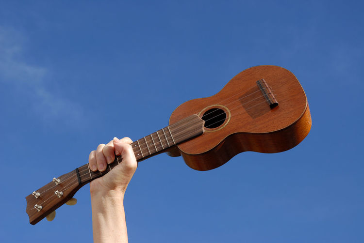 Low angle view of hand playing guitar against blue sky