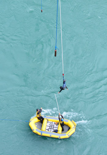 Person during bungy jump in New Zealand Adventure Blue Bungy Jumping Commercial Sign Day Kawarau Bridge Leisure Activity Lifestyles Nature New Zealands Outdoors Rippled Sport Tranquility Water Yellow