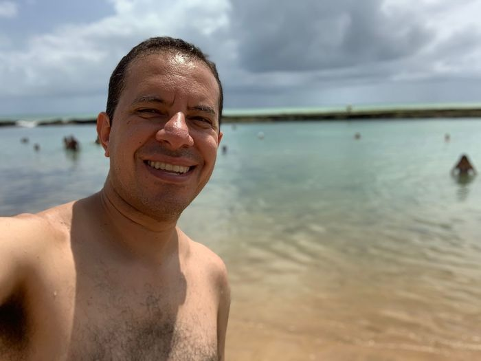 Portrait Of Shirtless Man At Beach Against Sky