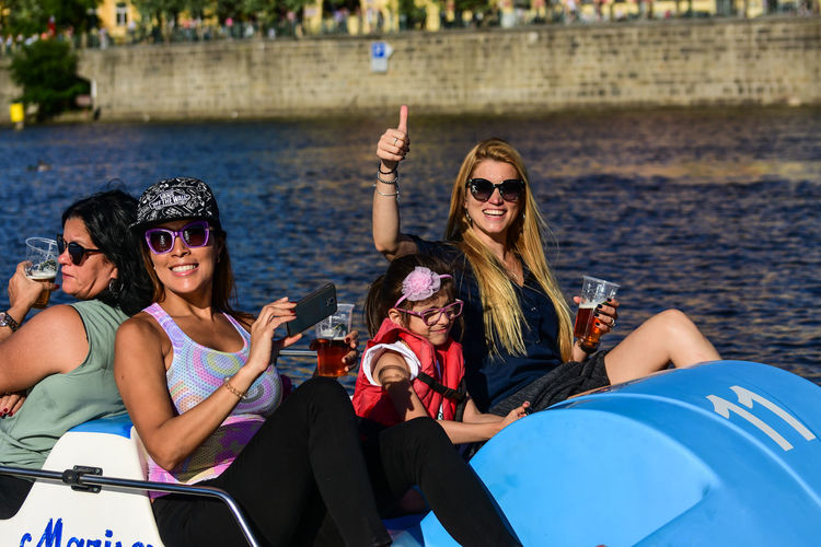 Enjoyment Fashion Friendship Fun Glasses Group Of People Happiness Leisure Activity Lifestyles Outdoors Sitting Smiling Sunglasses Togetherness Transportation Water Women Young Adult Young Women