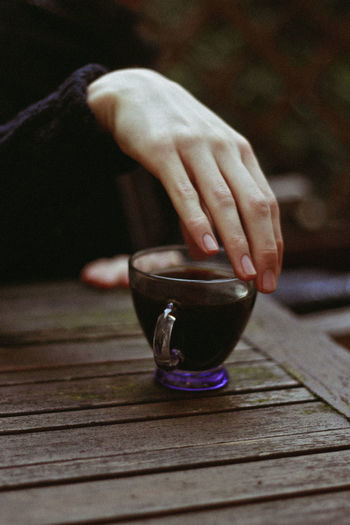 Cropped Hand Of Woman With Coffee On Wooden Table In Cafe