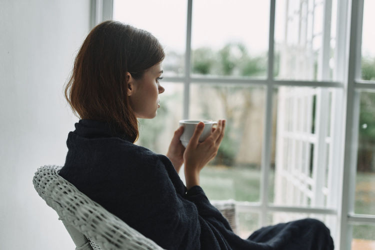 Side view of young woman using laptop on window