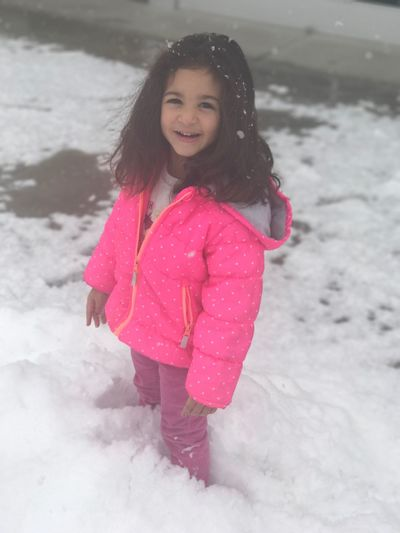 Portrait of smiling girl standing on snow