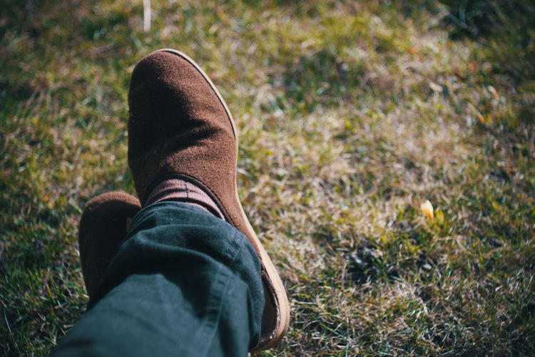 Low Section Of Man Wearing Shoes While Sitting On Grassy Field