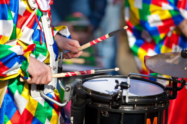 Midsection of drummer playing drum during carnival