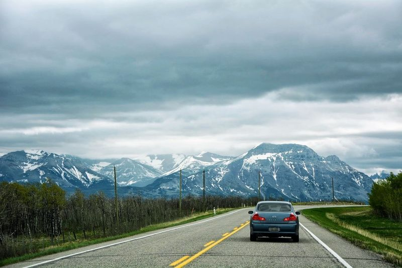 Cars on road by snowcapped mountains against sky