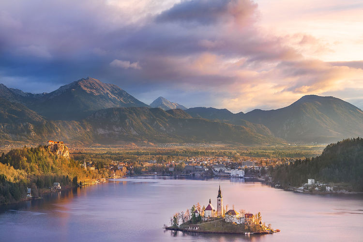 Lake Bled and its island at sunrise - Colorful sunrise over the Bled lake, its surrounding hills, its island and the Karawanks mountains in the background, situated in Slovenia. Slovenia Tourist Attraction  Beauty In Nature Cloud - Sky Day Destination Europe Island Lake Mountain Mountain Range Nature No People Outdoors Purple Sky Scenics Sky Sunrise Sunset Tranquil Scene Tranquility Water