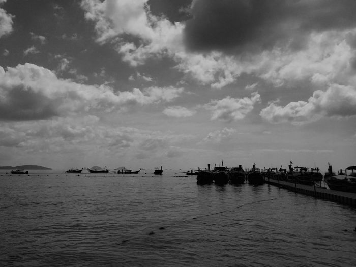 Boats in calm sea against cloudy sky