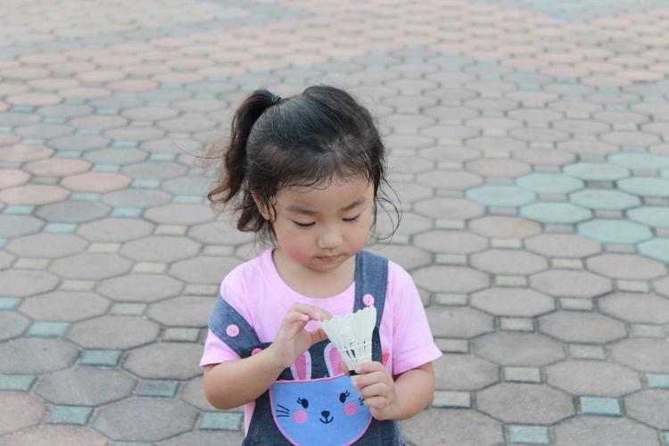Girl holding shuttlecock on walkway