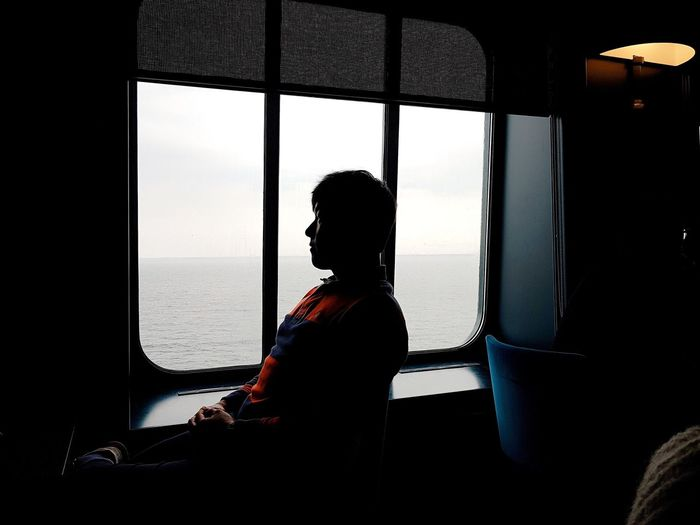 Side view of man sitting by window in ship
