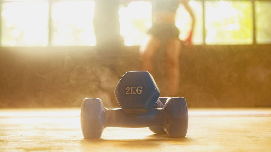 Dumbbell images placed in fitness with people exercising behind the concept of exercise for good health. Sunlight Focus On Foreground Outdoors Back Lit Sport Sitting Lifestyles Communication Still Life Brightly Lit Dumbbell Fitness Training Fitness Model Fitness Time Exercise Good Health