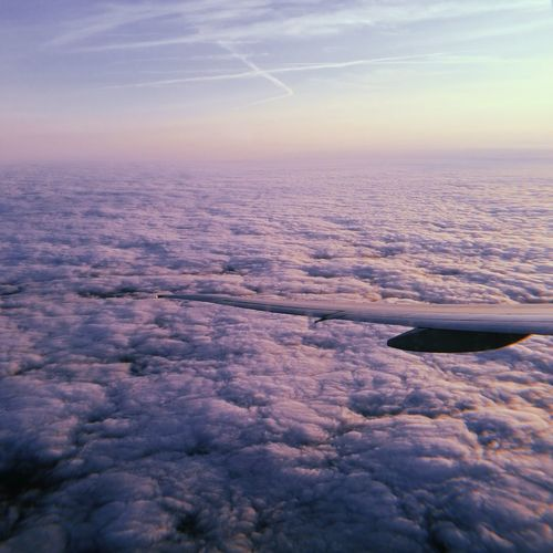 Cropped image of aircraft wing flying over cloudscape against sky during sunset