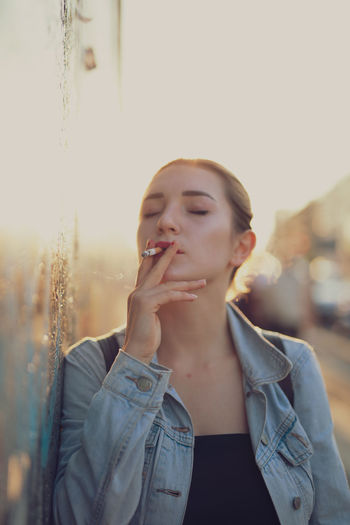 Young woman smoking while standing by wall in city against sky