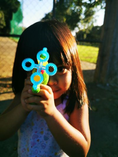 Portrait of a girl holding a bubble wand.