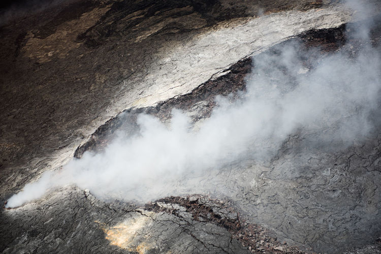 Toxic fumes billow out of a vent at the erupting Kilauea volcano in Hawai'i. The surrounding landscape is barren, black rock, tinged with yellow from the sulphur that emerges with volcanic explosions and venting. Aerial Shot Caldera Forces Of Nature Hawaii Natural Nature Rock Smoke Steam Barren Beauty In Nature Crater Erupting Eruption Fumes Grey High Angle Landscape Lava Natural Forces Vent Volcano