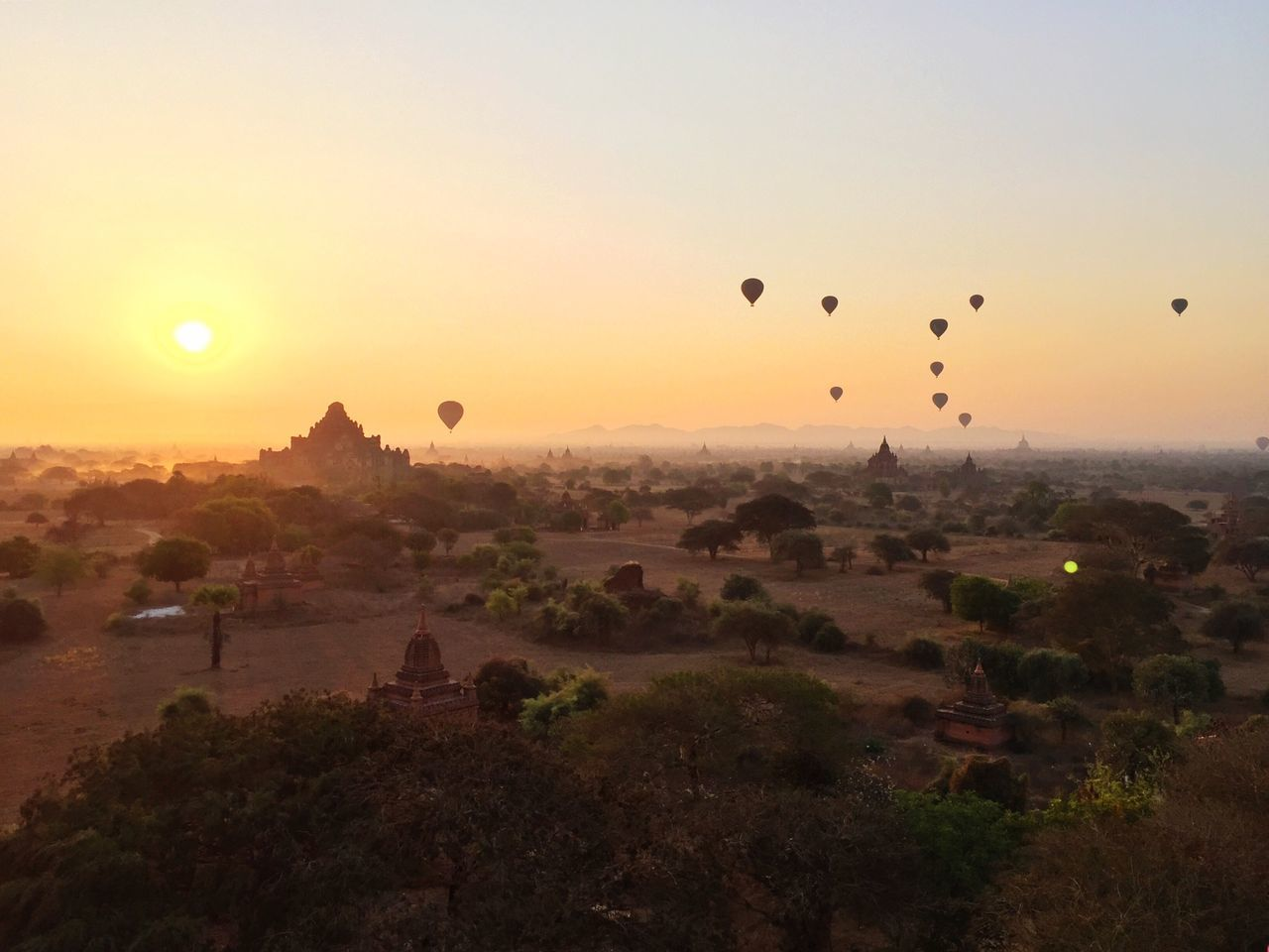Stupas and hot air balloons during sunset