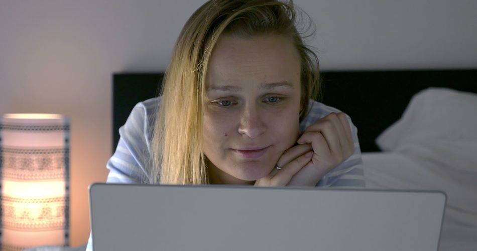 Portrait of teenage girl using laptop at home