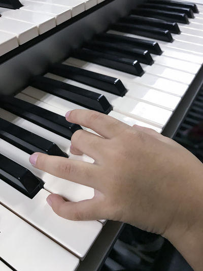 Close-up of hand playing synthesizer