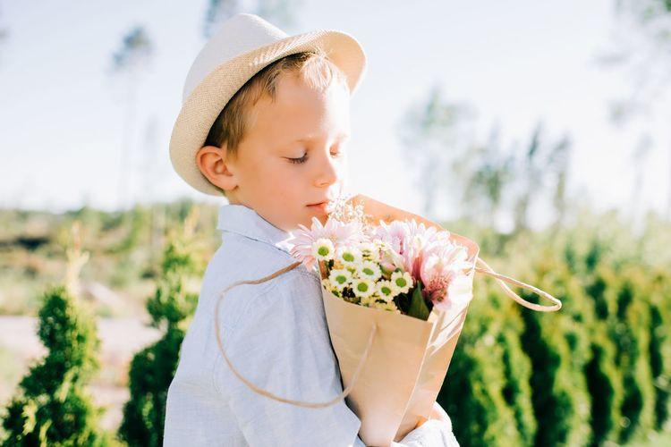 Cute girl holding flower against blurred background