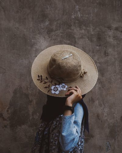 High angle view of person holding hat against wall