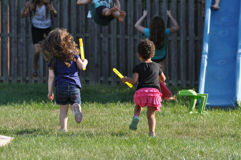 Two Young Girls Running Through a Yard Family Playing Games Relationship Child Childhood Curly Hair Full Length Fun Outdoors People Playing Spring Summer Togetherness