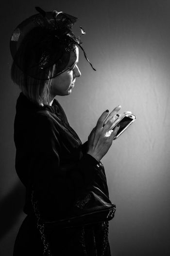 Side view of mid adult woman using mobile phone against gray background