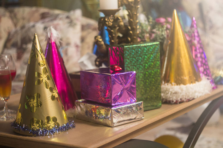 Close-up of colorful gift boxes and party hats on table during christmas