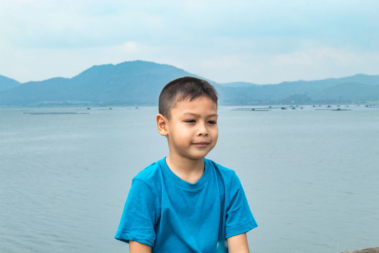 Boy looking away while sitting against sea