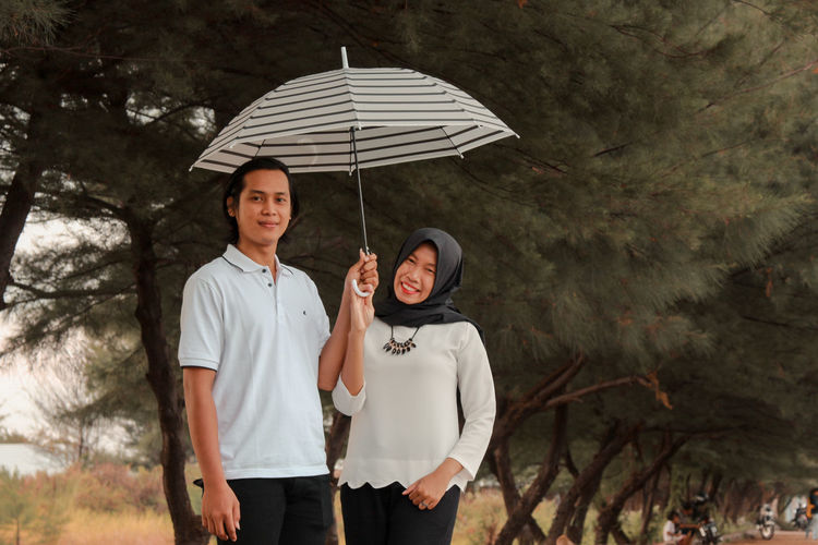 Adult Two People Men Togetherness Umbrella Heterosexual Couple Couple - Relationship Women Protection Love Males  Happiness Emotion Nature Standing Positive Emotion Smiling People Mature Adult Outdoors