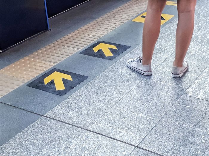 Low section of woman standing on tiled floor by arrow symbols