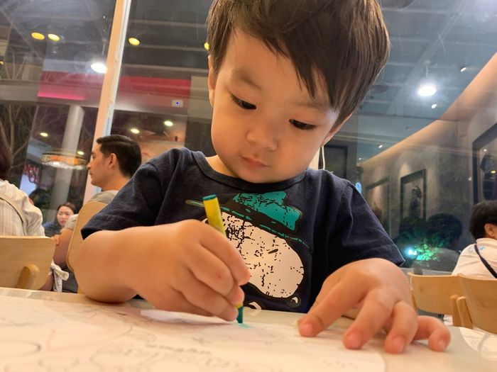 Child Childhood Real People Headshot Lifestyles Men Indoors  Restaurant Front View Males  Boys Casual Clothing Table Illuminated One Person Portrait Holding Leisure Activity Innocence Glass