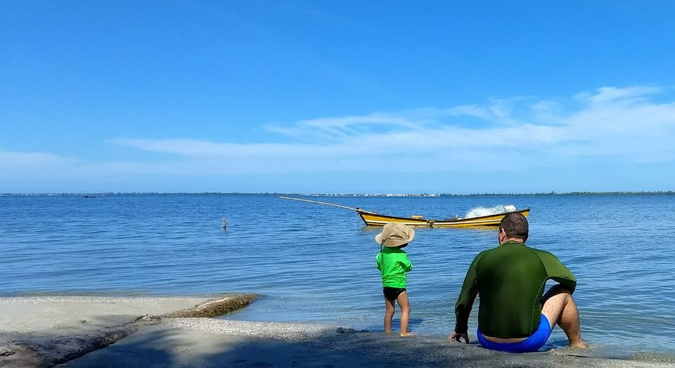 Rear view of father and child at beach against sky