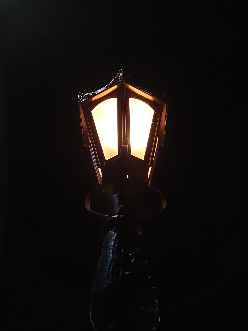 LOW ANGLE VIEW OF ILLUMINATED LAMP IN DARK ROOM