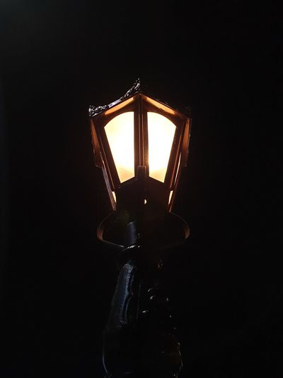 Low angle view of illuminated lamp against black background