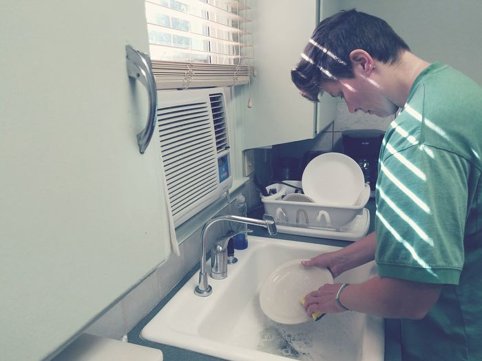 Woman Washing Dishes At Kitchen Sink