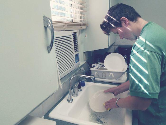 Woman washing dishes at kitchen sink