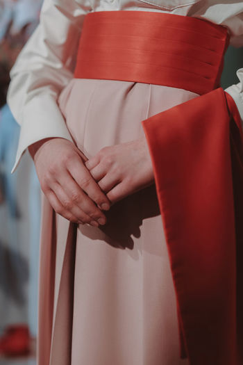 Cropped figure of fashion model woman wearing beautiful pink long clothes with red belt. fashion