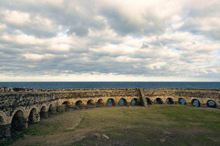 Yoros castle by sea against cloudy sky