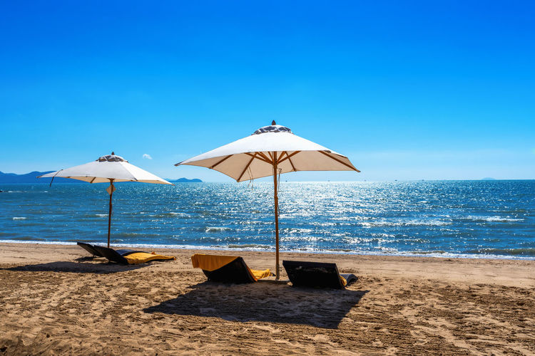 Chairs and umbrella on a tropical beach. Sea Beach Water Land Sky Scenics - Nature Horizon Over Water Horizon Beauty In Nature Parasol Sand Blue Tranquility Tranquil Scene Shade Nature Sunlight Umbrella Protection No People Outdoors