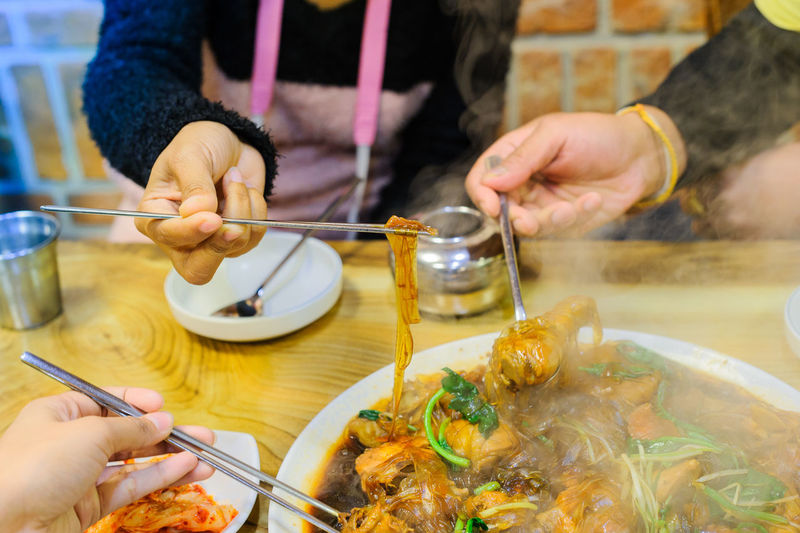 Close-up of family eating traditional korea food,ginseng chicken soup