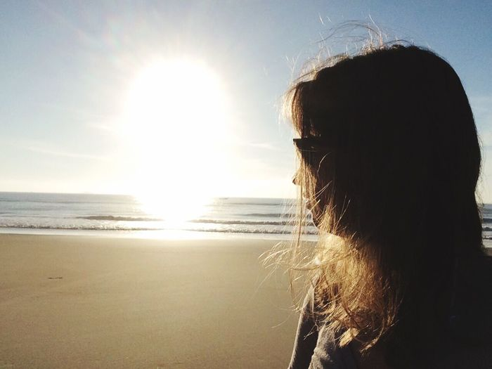 Close-up of woman standing at beach against sky