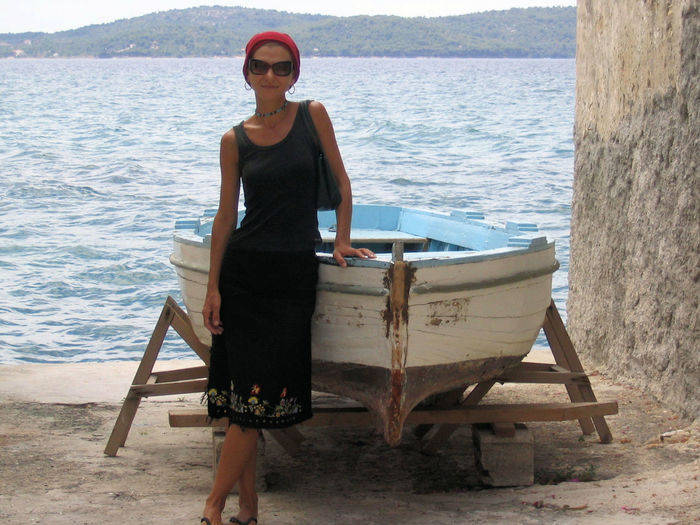 Portrait of woman standing by boat at beach