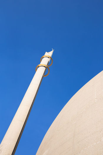 Low angle view of minaret against clear blue sky