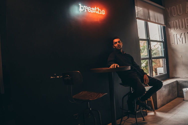 man in black Sitting One Person Seat Real People Young Adult Young Men Full Length Chair Business Front View Indoors  Lifestyles Communication Casual Clothing Leisure Activity Men Illuminated Contemplation Dark Malang Cafe