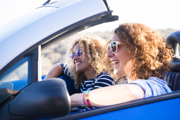 Couple of curly cheerful woman smiling and having fun together enjoying the travel vacation driving the car - people on the move in convertible vehicle in sunny day of summer Transportation Mode Of Transportation Car Motor Vehicle Smiling Happiness Sitting Togetherness Travel Young Adult Emotion Headshot Women Young Women Leisure Activity Fun Driving Portrait Journey Road Trip Positive Emotion Outdoors Two People Enjoying Life Laugh Curly Hair Caucasian Happiness Freedom Casual Clothing Cheerful Travel Destinations Vacations Vehicle Summer Sunlight Females Mother Adventure Open Bonding 40-44 Years Tropical