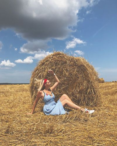 Woman with arms raised sitting against haystack