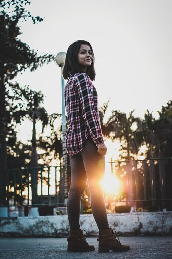 Young woman standing by tree against sky during sunset