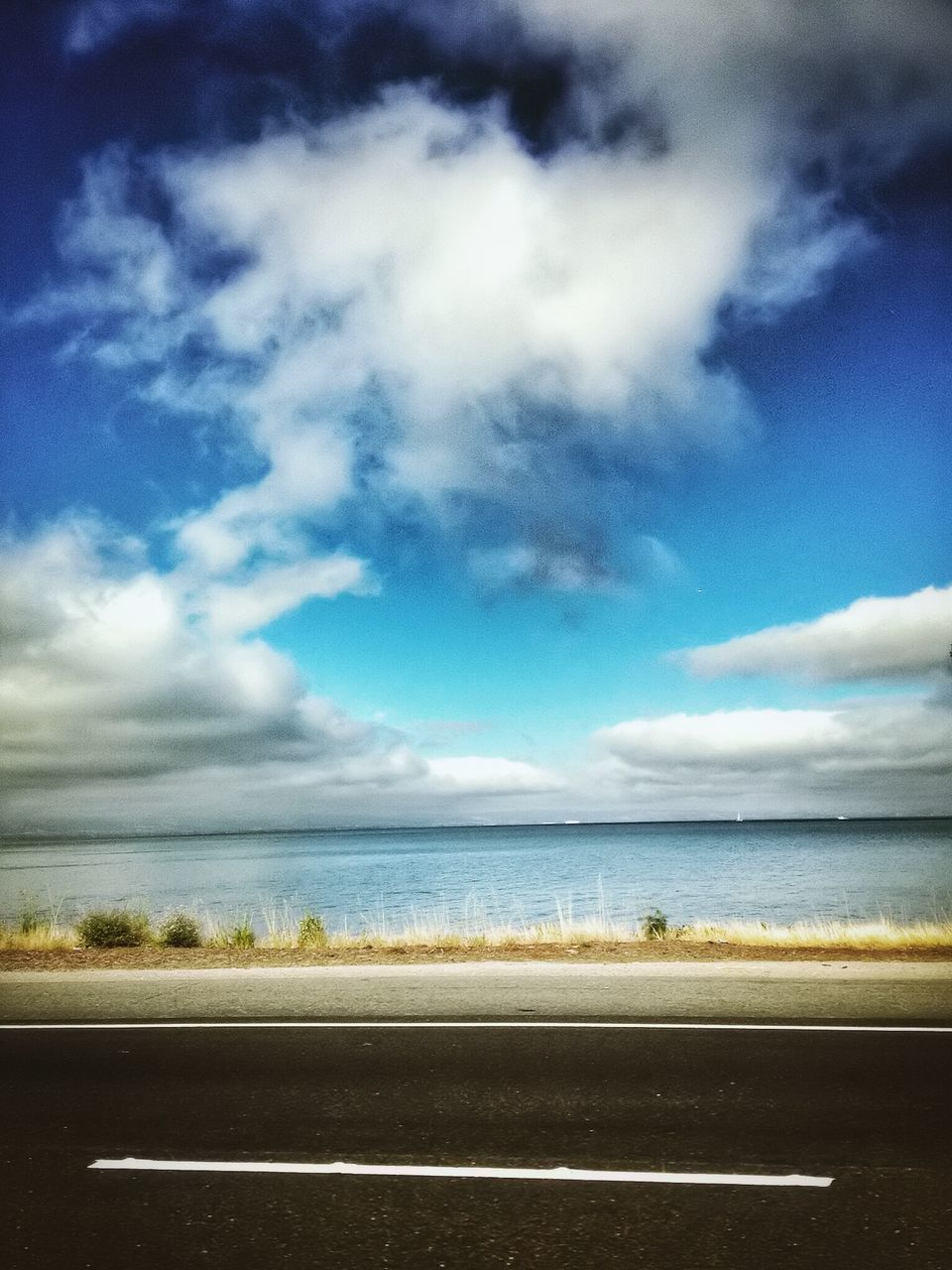 sky, cloud - sky, road, sea, scenics, tranquility, horizon over water, day, nature, no people, tranquil scene, beauty in nature, transportation, outdoors, beach, water